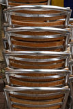 Stacked Aluminium Silver Chairs Outside a Cafe. Stacked silver aluminium and wood chairs outside a cafe Royalty Free Stock Image