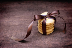 Stacked apple chip cookies taped with silk ribbon. Close up of stacked apple chip cookies taped with silk ribbon on rustic wooden background Stock Photos