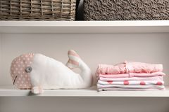 Stacked baby clothes and plush toy. On shelf stock image