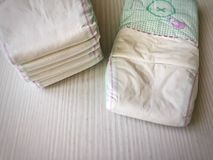 Stacked baby diaper. On a white wooden table stock image