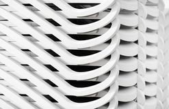 Stacked beach loungers. Stacked white plastic beach loungers. Abstract background royalty free stock photos