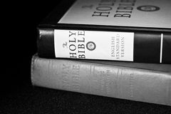 Stacked Bibles. Black and white photo of two different version of the holy Bible on a black table cloth royalty free stock photo