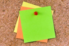 Stacked Blank Colored Post-its Pushpin. Topview stacked square blank colored post-its or postits affixed on a cork board with red pushpin Stock Photos