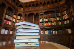 Stacked books with library in the background. Stacked books on wood table with library in the background Royalty Free Stock Image