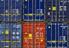 Cargo containers frontal view. Stacked boxes of cargo containers at the dockside waitng to be emptied or reused and rented and sold agian. trade long distance royalty free stock photos