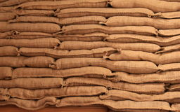 Stacked burlap sandbags under soft lights Stock Photos