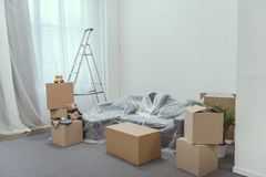 stacked cardboard boxes, ladder and toys in empty room Royalty Free Stock Images