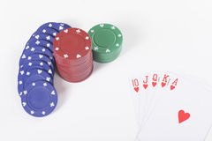 Stacked casino chips with a winning poker hand. In hearts showing a straight royal flush in a lucky streak at gambling viewed from above on white Stock Photography