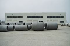 Stacked cement pipes at concrete factory. Outdoors warehouse . Industrial production of cement products. Industry manufacturing concept royalty free stock images