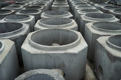 Stacked cement pipes at concrete factory. Outdoors warehouse . Industrial production of cement products. Industry manufacturing concept stock photos