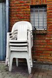 Stacked chairs. A stack of white plastic chairs on the wall Stock Photo