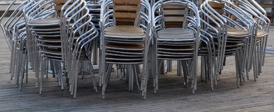 Stacked chairs on decking. Wide angled view of stacked metal chairs on wooden decking Royalty Free Stock Image