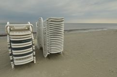Stacked chairs, empty beach. Pile of stacked white plastic lounge chairs on empty sea beach. Overcast sky. Summer vacation. Copy space. Black sea Stock Images