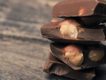 Stacked chocolate bars. Close up of stacked chocolate bars on a wooden table, vintage color toned Stock Image