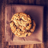 Stacked chocolate chip cookies on brown napkin over wooden backg Royalty Free Stock Photography
