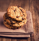 Stacked chocolate chip cookies on brown napkin over wooden backg Royalty Free Stock Photo