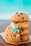 Stacked chocolate chip cookies with ribbon, on blue background Royalty Free Stock Photography