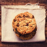 Stacked chocolate chip cookies on white linen napkin on wooden t Royalty Free Stock Photography