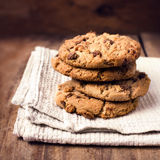 Stacked chocolate chip cookies on white napkin in country style. Royalty Free Stock Photos