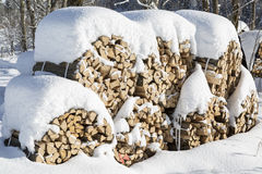 Stacked chopped firewood covered by snow in winter Royalty Free Stock Image