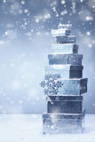 Stacked Christmas gifts in winter snowfall Royalty Free Stock Images