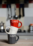 Stacked coffee cup and  vintage coffeepot on kitchen stove. Background Stock Photography