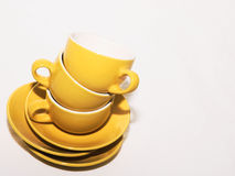Stacked Coffee Cups. Three yellow coffee cups and their saucers stacked for washing Royalty Free Stock Photos