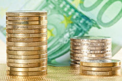 Stacked coins and euro banknote Royalty Free Stock Photos