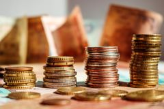 Stacks of coins in the form of growth graph. Business concept. Blurred background with banknotes stock images