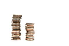 Stacked Coins Money. Two stacks of coins against white for use in financial and banking concepts Stock Images