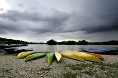 Stacked of the colorful canoes near the lake. dramatic and cloudy sky. stock photos