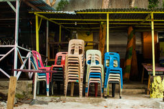 Stacked colorful chairs of a closed island bar. On the beach Royalty Free Stock Photography
