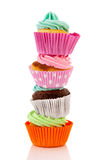 Stacked colorful cupcakes. Colorful stacked cupcakes with butter cream isolated over white background Stock Photo