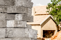 Stacked concrete bricks infront of house bein build Royalty Free Stock Photo