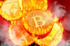 Stacked cryptocurrency coins. Conceptual pictures of cryptocurrency coins bursting into flammes, illustrating crypto-currency market crash Stock Photo