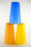 Stacked cups. Three colorful plastic cups stacked in pyramid shape; studio background royalty free stock photography