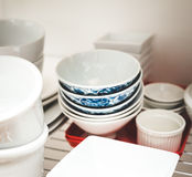 Stacked dishes in kitchen. Dishes stacked on shelves in a kitchen area Royalty Free Stock Photography