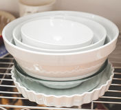 Stacked dishes in kitchen. Dishes stacked on shelves in a kitchen area Stock Photos