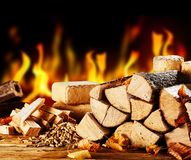 Stacked dried logs in front of a burning fire stock photos