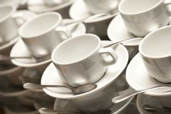 Stacked empty teacups with teaspoons Stock Images