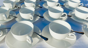 Stacked empty teacups with teaspoons at a function over white ba Royalty Free Stock Image