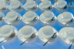 Stacked empty teacups with teaspoons at a function over white ba Royalty Free Stock Photo