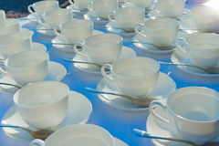 Stacked empty teacups with teaspoons at a function over white ba Stock Photos