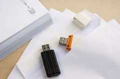 Stacked envelopes and flash drives Stock Photo