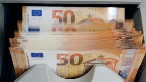 Stacked euro banknotes are getting calculated. 4K stock video footage