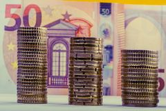 Stacked euro coins against a paper denomination worth fifty euro. S. Euro money.  Currency of the European Union Stock Photos