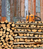 Stacked firewood with chain saw Royalty Free Stock Images