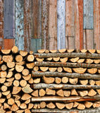 Stacked firewood colorful batten wall. Stacked firewood heap against old weathered colorful wooden wall royalty free stock photography
