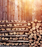 Stacked firewood heap afternoon light. Stacked firewood heap against old weathered wooden wall royalty free stock photography