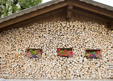Stacked firewood on house in Alps Stock Photos